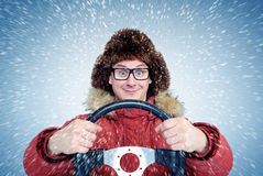 Happy Man in winter clothes with a steering wheel, snow blizzard. Concept car driver Stock Photography