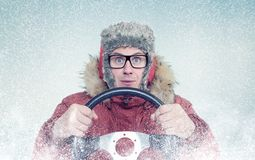 Happy man in winter clothes with a steering wheel, snow blizzard. Concept car driver Stock Image