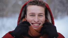 Happy man in winter jacket with hood outdoors stock footage