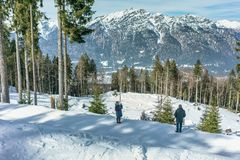 Happy man and woman admire the alpine mountains on a bright winter day. royalty free stock photo