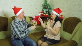 Happy man and woman celebrate Christmas at home with glasses of champagne and Bengali candles stock footage