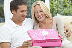 Happy Man & Woman Couple Opening Birthday Present Royalty Free Stock Photos