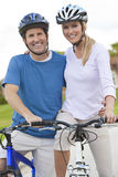 Happy Man & Woman Couple Riding Bikes Royalty Free Stock Photography