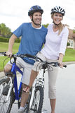 Happy Man & Woman Couple Riding Bikes Stock Image