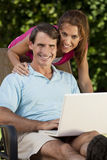 Happy Man and Woman Couple Using Laptop Computer. Portrait shot of an attractive, successful and happy middle aged man and woman couple in their thirties Royalty Free Stock Images