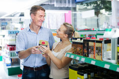 Happy man and woman customers choosing can with protective furni Stock Photo