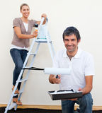Happy man and woman decorating a room. After move in Royalty Free Stock Photography