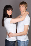 Happy man and woman dressed in white shirts hug Royalty Free Stock Image