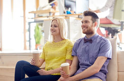 Happy man and woman drinking coffee in office Stock Image
