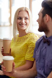 Happy man and woman drinking coffee in office Stock Photography