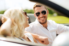 Happy man and woman driving in cabriolet car. Leisure, road trip, dating, couple and people concept - happy men and women driving in cabriolet car outdoors Royalty Free Stock Photography