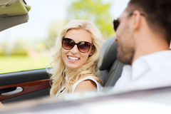 Happy man and woman driving in cabriolet car. Leisure, road trip, dating, couple and people concept - happy men and women driving in cabriolet car outdoors Royalty Free Stock Image