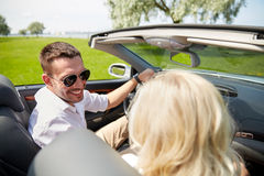 Happy man and woman driving in cabriolet car. Leisure, road trip, dating, couple and people concept - happy men and women driving in cabriolet car outdoors Royalty Free Stock Images