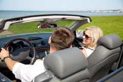 Happy man and woman driving in cabriolet car Stock Photos