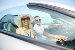 Happy man and woman driving in cabriolet car. Leisure, road trip, dating, couple and people concept - happy men and women driving in cabriolet car outdoors Stock Photo