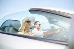 Happy man and woman driving in cabriolet car. Leisure, road trip, dating, couple and people concept - happy men and women driving in cabriolet car outdoors Stock Photography