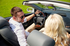 Happy man and woman driving in cabriolet car. Leisure, road trip, dating, couple and people concept - happy men and women driving in cabriolet car outdoors Royalty Free Stock Photos