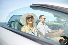 Happy man and woman driving in cabriolet car. Leisure, road trip, dating, couple and people concept - happy men and women driving in cabriolet car outdoors Stock Photos