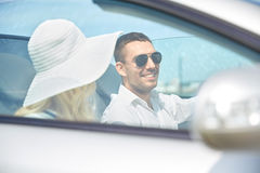 Happy man and woman driving in cabriolet car. Leisure, road trip, dating, couple and people concept - happy men and women driving in cabriolet car outdoors Stock Images