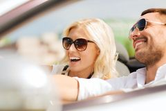 Happy man and woman driving in cabriolet car. Road trip, dating, leisure, couple and people concept - happy men and women driving in cabriolet car outdoors Royalty Free Stock Photo