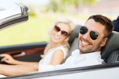 Happy man and woman driving in cabriolet car. Road trip, dating, leisure, couple and people concept - happy men and women driving in cabriolet car outdoors Royalty Free Stock Images