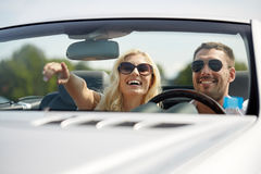 Happy man and woman driving in cabriolet car. Road trip, travel, couple and people concept - happy men and women driving in cabriolet car outdoors Stock Image
