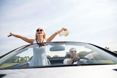 Happy man and woman driving in cabriolet car Stock Image