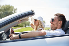 Happy man and woman driving in cabriolet car. Road trip, travel, dating, couple and people concept - happy men and women driving in cabriolet car outdoors Stock Photos