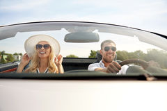 Happy man and woman driving in cabriolet car. Road trip, travel, dating, couple and people concept - happy men and women driving in cabriolet car outdoors Stock Image