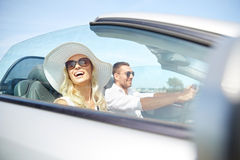 Happy man and woman driving in cabriolet car. Road trip, travel, dating, couple and people concept - happy men and women driving in cabriolet car outdoors Royalty Free Stock Photography