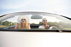 Happy man and woman driving in cabriolet car. Road trip, travel, dating, couple and people concept - happy men and women driving in cabriolet car outdoors Stock Photography