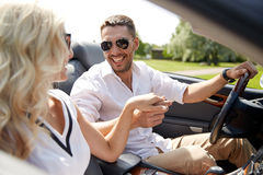 Happy man and woman driving in cabriolet car. Road trip, travel, dating, couple and people concept - happy men and women driving in cabriolet car outdoors Stock Photo