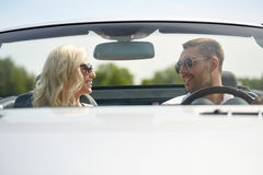 Happy man and woman driving in cabriolet car. Road trip, travel, dating, couple and people concept - happy men and women driving in cabriolet car outdoors Royalty Free Stock Photo