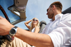 Happy man and woman driving in cabriolet car. Road trip, travel, dating, couple and people concept - happy men and women driving in cabriolet car outdoors Royalty Free Stock Photos
