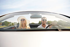 Happy man and woman driving in cabriolet car. Road trip, travel, dating, couple and people concept - happy men and women driving in cabriolet car outdoors Royalty Free Stock Images