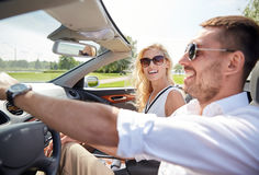 Happy man and woman driving in cabriolet car Stock Images