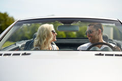 Happy man and woman driving in cabriolet car. Road trip, travel, dating, couple and people concept - happy men and women driving in cabriolet car outdoors Stock Images