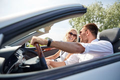 Happy man and woman driving in cabriolet car. Road trip, travel, dating, couple and people concept - happy men and women driving in cabriolet car outdoors Royalty Free Stock Image