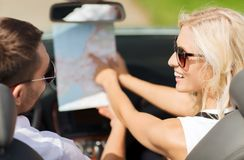 Happy man and woman driving in cabriolet car. Road trip, travel, leisure, couple and people concept - happy men and women driving in cabriolet car with map Stock Images