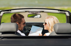 Happy man and woman driving in cabriolet car. Road trip, travel, leisure, couple and people concept - happy men and women driving in cabriolet car with map Royalty Free Stock Image