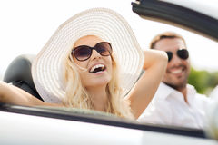 Happy man and woman driving in cabriolet car. Transport, leisure, road trip and people concept - happy men and women driving in cabriolet car outdoors Stock Photos