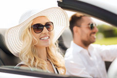 Happy man and woman driving in cabriolet car. Transport, leisure, road trip and people concept - happy men and women driving in cabriolet car outdoors Royalty Free Stock Photography