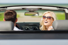 Happy man and woman driving in cabriolet car. Transport, road trip, leisure, couple and people concept - happy men and women driving in cabriolet car outdoors Stock Image