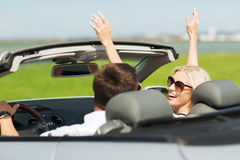 Happy man and woman driving in cabriolet car. Transport, road trip, leisure, couple and people concept - happy men and women driving in cabriolet car outdoors Stock Images