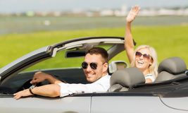 Happy man and woman driving in cabriolet car. Transport, road trip, leisure, gesture and people concept - happy men and women driving in cabriolet car and waving Stock Image