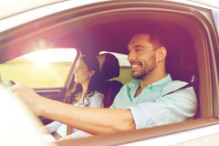 Happy man and woman driving in car. Leisure, road trip, travel, family and people concept - happy men and women driving in car Royalty Free Stock Image