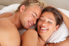 Happy man and woman enjoying in bed Royalty Free Stock Images