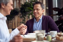 Happy man and woman enjoying together in cafe. Enjoyable meetings. Close up portrait of happy smiling aged gentleman and lady holding hands while enjoying dinner royalty free stock images