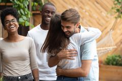 Happy man and woman greeting hugging at multi-ethnic friends meeting stock image