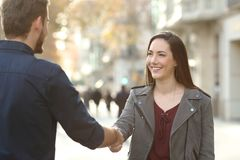 Happy man and woman handshaking in a city street. Happy men and women handshaking closing deal in a city street stock photos